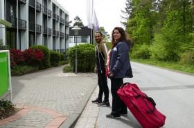 Magdalena Lamus mit Koffer vor Haus Neuland