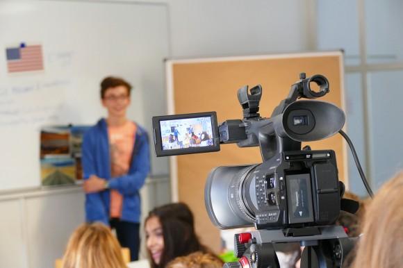 Junge steht vor dem Seminar - Eine Kamera im Vordergrund
