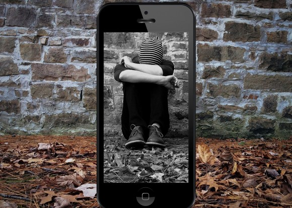 Trauriger Junge umrandet von Smartphone Display.