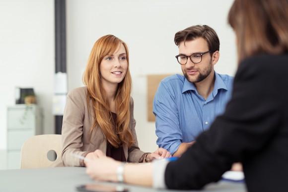 Mann und Frau in Gespräch mit Lehrerin.