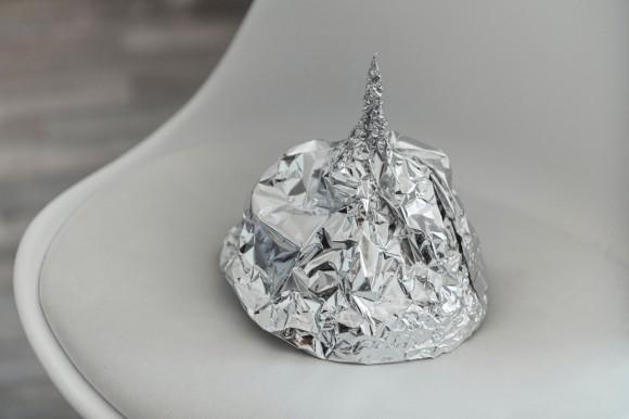 Ein Hut aus Alu-Folie liegt auf einem Stuhl.