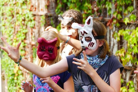 Mädchen mit selbtsgebastelten Tiermasken.